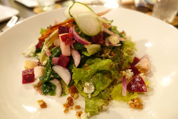 Warm spinach, wild mesclun, pear and blue cheese salad, with pickled beets and candied pili nuts